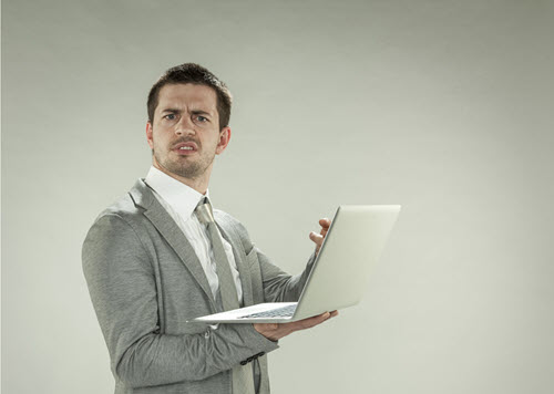 Confused man looking at laptop computer